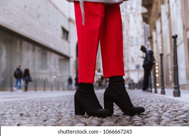 Close up of black women's boot socks on the italian street. Red pants and a gray raincoat outfit