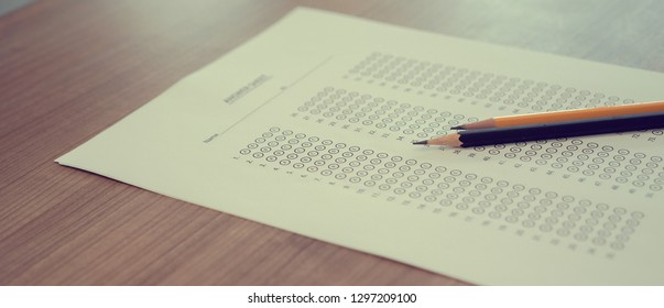 close up black and yellow pencil over exam answer sheet paper with multiple choice on wood table for world literacy day and education concept