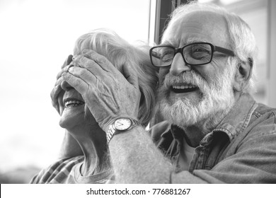 Close up black-and-white portrait of two excited pensioners. Old husband preparing wife for surprise moment