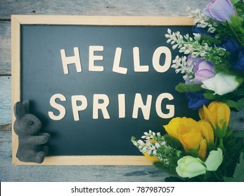 close up blackboard with hello spring wooden text, beautiful flower and bunny on old wood table, happy easter day and march break holiday concept, top view, process vintage tone