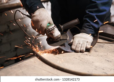 Close up of blacksmith grindering a metal plate holding an angle grinder. The blacksmith work clothes in white blacksmith gloves grindering a metal plate
