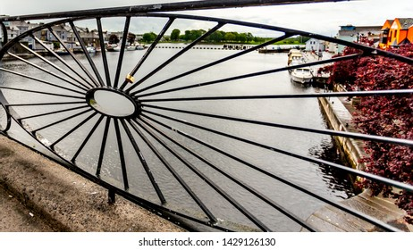 Close up of a blacksmith railing with a padlock and the river Shannon, boats anchored at the dock in the town of Athlone in the county of Westmeath, Ireland