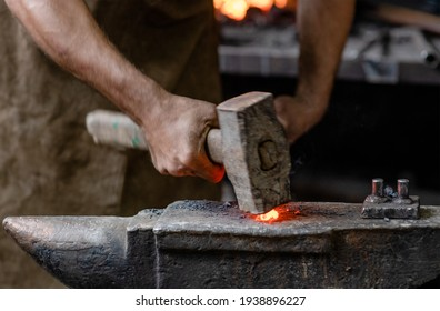 Close up blacksmith working metal with hammer on the anvil in the forge