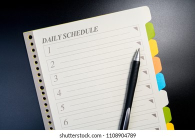 Close up of blank daily schedule list with pen on black table for business. Planing document for business.