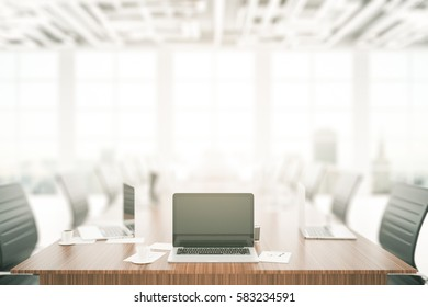 Close up of blank laptop placed on wooden conference table in interior with daylight. Mock up, 3D Rendering. Meeting concept