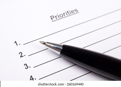 close up of blank list of priorities and metal pen
