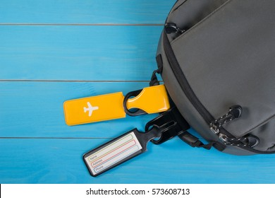 Close up of blank luggage tag label on suitcase or bag with travel insurance. Travel insurance label tied to a backpack.
