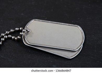 close up of blank military dog tags with chain on black slate
