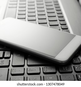 Close up of blank mobile, smart phone on the laptop