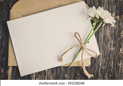 Close up of blank white greeting card with brown envelope and wither Mum flowers on wooden table with vintage and vignette tone