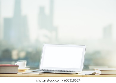 Close up of blank white laptop placed on desktop with books, supplies and other items on blurry city view background. Mock up