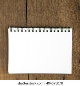 The close up of blank white notebook on wooden plank background.