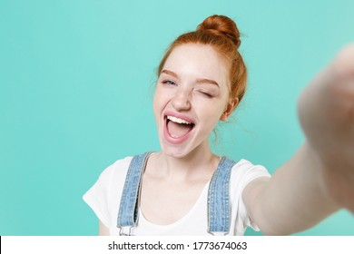 Close up of blinking young readhead girl in casual denim clothes posing isolated on blue turquoise background studio. People lifestyle concept. Mock up copy space. Doing selfie shot on mobile phone
