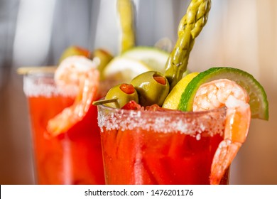 close up of a bloddy mary cocktail served on a wooden bar top garnished with a salted rim veggies and a shrimp