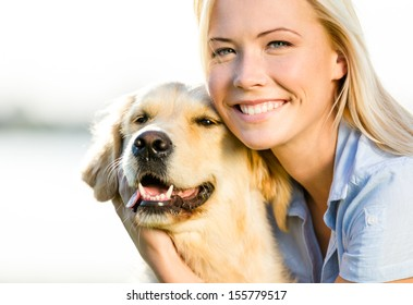 Close up of blond woman embracing golden retriever
