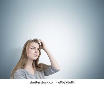 Close up of a blonde businesswoman scratching her head and thinking. She is wearing a gray sweater and trying to recall an idea. Gray wall background, mock up