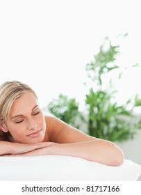 Close up of a blonde smiling woman lying on a lounger with closed eyes in a wellness center