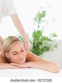Close up of a blonde woman relaxing on a lounger enjoys a massage in a wellness center