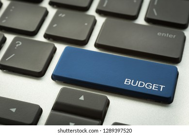 Close up blue button laptop keyboard selective focus on word BUDGET. Accounting, marketing plan, business project and financial concepts.
