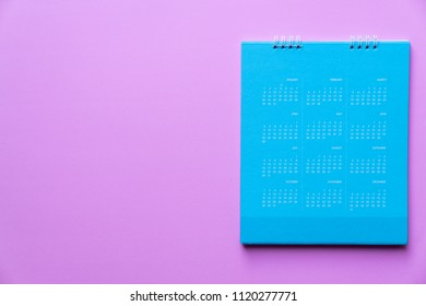 close up of blue calendar on pink background, planning for business meeting or travel planning concept