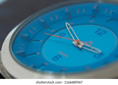close up blue clock face. hand of the clock showing hours, minutes and seconds. selective focus with blurred foreground and background.