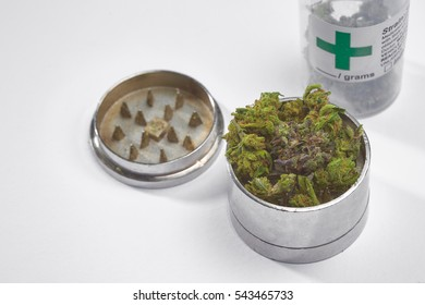 Close up of Blue Cookies marijuana buds with grinder on white background