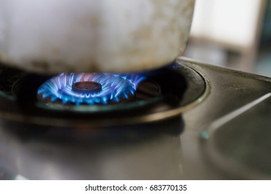 Close up Blue Flames on the cooking stove with pot on top in the kitchen at the actual use.
