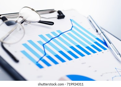 Close up of blue growth chart. Glasses and pen. Concept image of analyzing data.