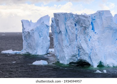 Close up of the blue ice cliffs and blue ice crevasses of a large blue ice tabular iceberg in the Errera Channel of Antarctica