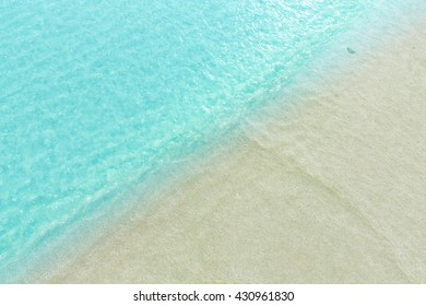Close up blue sea water waves on white sand beach in Thailand, Beautiful blue sea beach with white sand, Beautiful blue ocean beach close up shot, Clean beach with blue sea in Thailand,Sea background