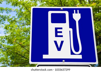 Close up of a Blue Sign indicating an Electric Vehicle Recharging Station with Green Trees in Background. Concept of Environment-friendly Modes of Transport