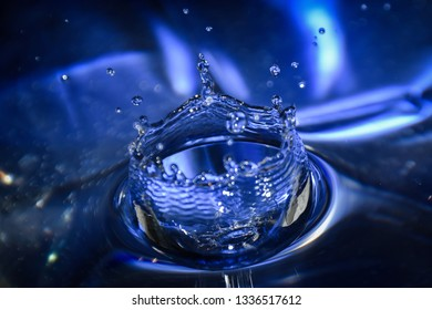 Close up of a blue water drop, macro photography. Falling water drop into water making crown.