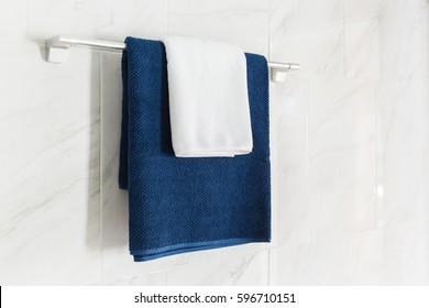 Close up blue and white color towels hanging on towel bar in bathroom