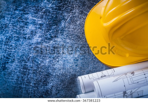 Nahaufnahme von Blueprint-Rollen und gelbem Hut auf metallisch gekratztem Oberflächenbau und Architektur-Konzept.