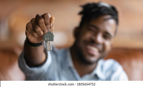 Close up blurred background view of excited African American male renter show new house keys buy first home. Happy biracial man tenant excited with moving relocation. Real estate, realty concept.