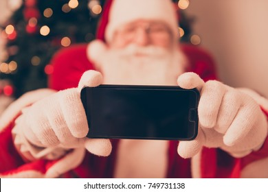 Close up blurred view of Saint Nicholas photographer in red traditional coat and head wear, taking shot on camera, indoors, making holly jolly x mas noel festive memories