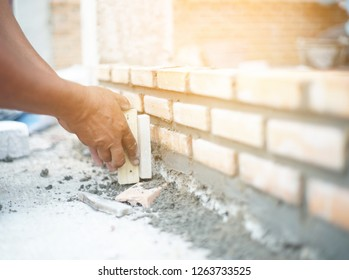 Close up blurry of industrial bricklayer installing bricks on construction site