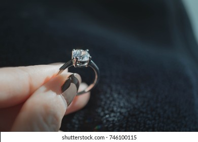 Close up of blurry woman's hand holding an elegant diamond ring.
