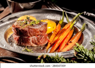 Close Up of Boar Steak Served on Metal Plate with Carrots on Wooden Tray with Evergreen Sprigs
