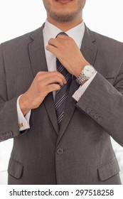 Close up of body of man in suit adjusting his tie
