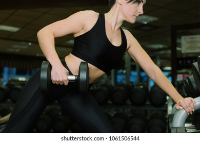 Close up - body sport woman. Sporty woman exercising with dumbbells in gym