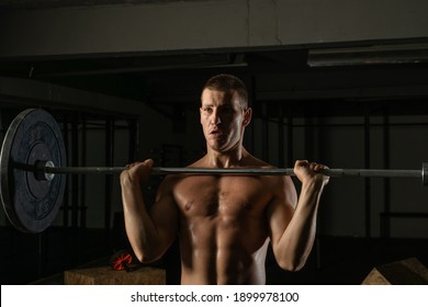 Close up bodybuilder doing barbel overhead shoulder press in a gym while flexing his muscles portrait.