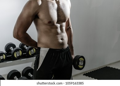 Close up of bodybuilder in gym. Sexy man do not were over blurred of exercise equipment. Can used for exercise to pumping up abs muscle concepts. Copy space for text.