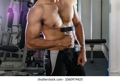 Close up of bodybuilder in gym. Sexy man  not wearing a shirt over blurred of exercise equipment. Can used for exercise to pumping up abs muscle concepts.