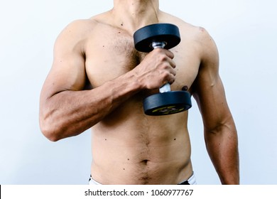 Close up of bodybuilder in gym. Sexy man not wearing a shirt over white wall holding dumbbell. Can used for exercise to pumping up abs muscle concepts.