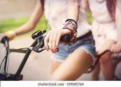 Close up of boho girls riding on bike