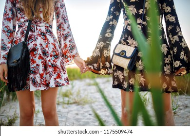 Close up boho style image of two woman holding hands, elegant vintage dresses and trendy bags, posing on the beach, fashion detailing.