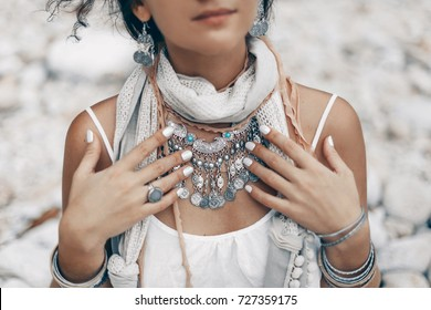 close up of boho styled woman on tropical beach with white pebble