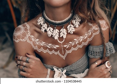 close up boho woman with traditional ornament outdoors at sunset