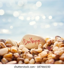 "Close Up ""Bon Voyage"" Text Written on the Stone at the Beach. Sea Pebble with Shallow Depth of Field and Beautiful Bokeh. Toned Photo. Summer Vacation Concept."
